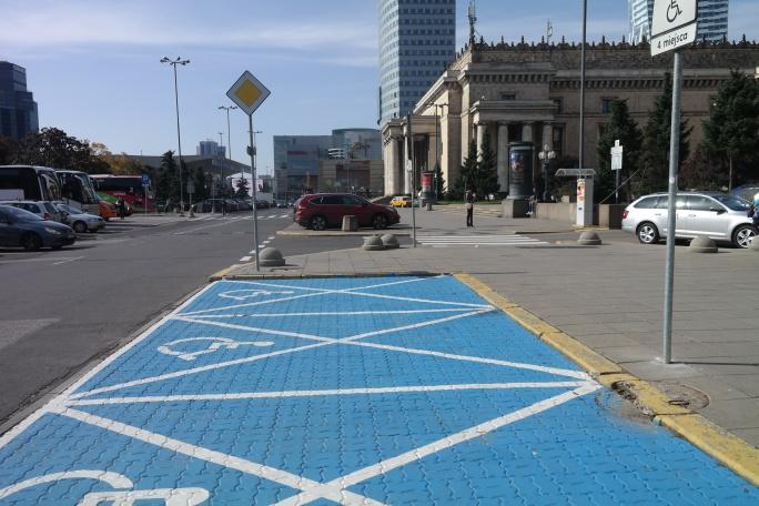 Miejsca parkingowe dla osób zniepełnosprawnością wotoczeniu zabytkowego PKiN wWarszawie, nawierzchnia zkostki brukowej